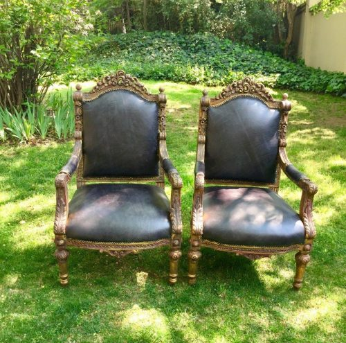 A Pair of French Louis XV Ornately carved and gilded armchairs in the Rococo influence with leather Upholstery