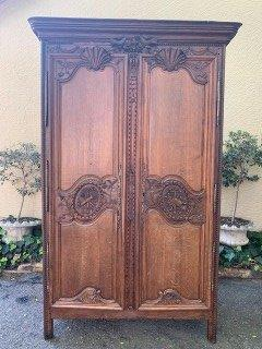 A French Provincial styled Ornately carved Armoire