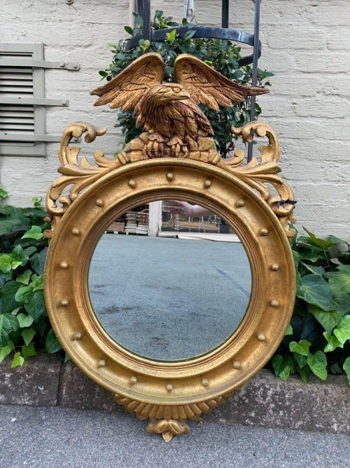 A circular framed 19thC style mirror with eagle crest