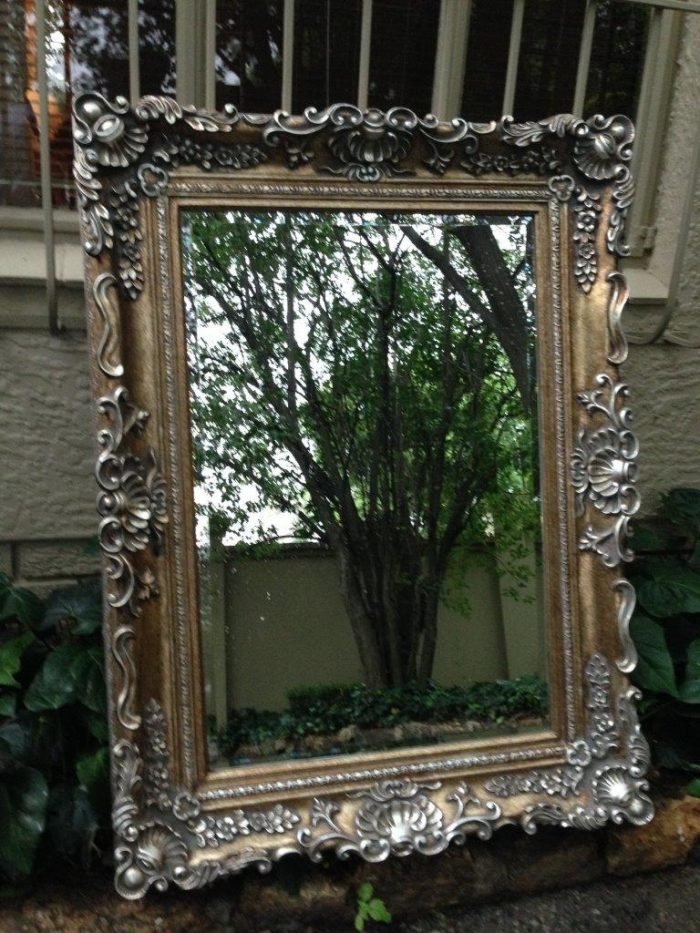 Elaborate mirror in silvered moulded frame