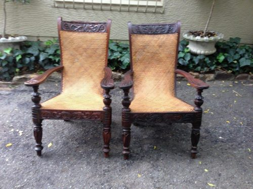 A pair of Plantation style arm chairs in rattan