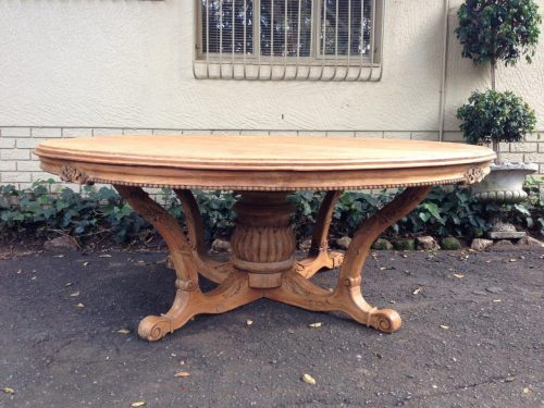 A heavily carved  English oak (wood stripped to natural colour) dining or entrance table on carved stem base