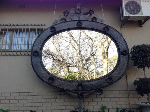 Oversized Statement Metal Mirror with carved bird detail on crown and base