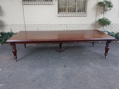 A Massive Victorian Style Mahogany Table with Castors and Supporting Leg