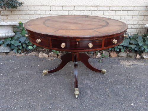 A Regency Mahogany Drum Table The top has gilt-tooled leather inset surface above eight drawers with brass lion-paw caps