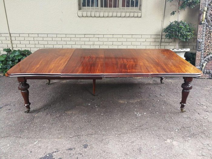 A 19th Century Mahogany Table Table Extends To A Fourteen-Seater With Two Extra Leaves And A Fifth Leg For Support On Brass Castors