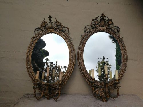 A Near Pair Of Early 20th Century French-Style Gilt-Painted Oval Mirrored Three-Light Wall Sconces