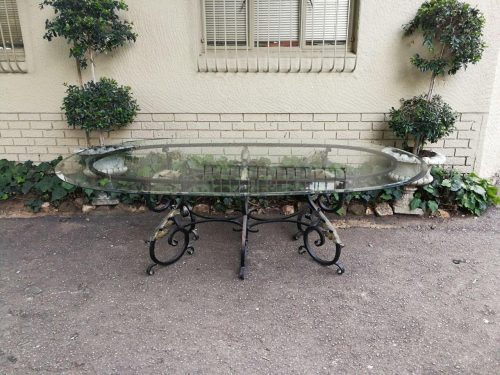 An Oval Glass Top And Metal Scrolled Base Outdoor Table