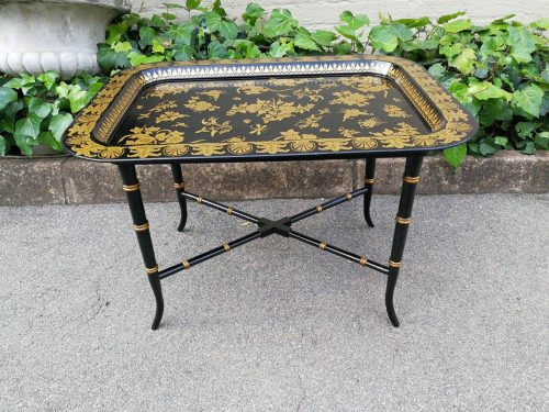 A Black Lacquered And Gilt Tray On An Ebonized And Gilt Stand