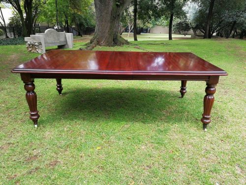 A Victorian mahogany extending ten-seater dining room table on brass castors and with winding crank
