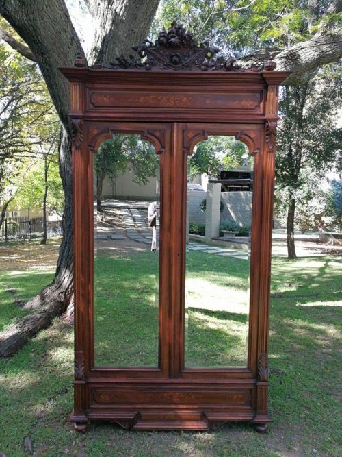 A 19th Century armoire with bevelled mirrors (keys to cabinet doors