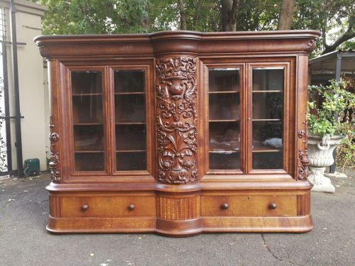 A Continental/ French oak heavily carved display/bookcase with secret side drawers