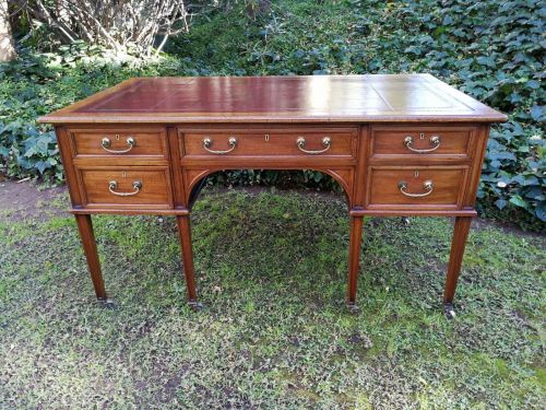 A 20th Century George lII style mahogany writing desk with gilt-tooled leather panels on casters