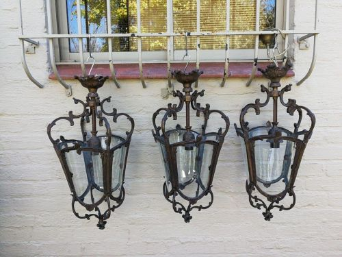 A set of 3 ornate wrought iron and glass hanging lanterns