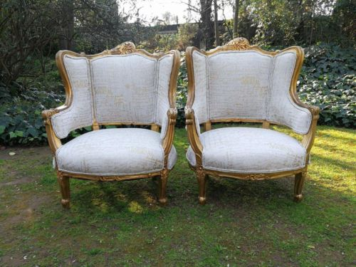 A Pair Of 20th Century French Style Gilt Bergere Armchairs Upholstered In A Custom-Made Hand Printed Linen With Gold Script Design By The Crown Collection