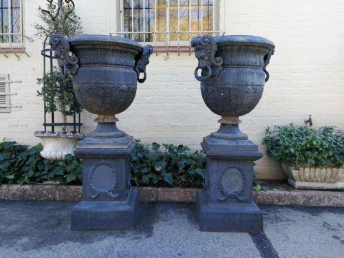 A Pair Of Cast Iron Urns On Plinths