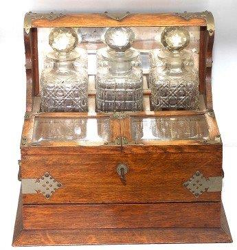 Late Victorian brass-mounted oak tantalus with three decanters