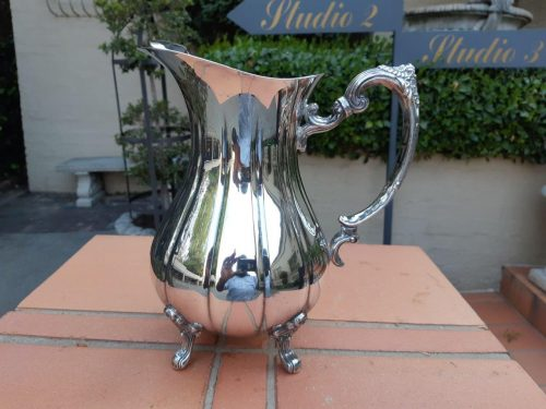 A Silver-Plated Water Jug On Styled Queen Anne Legs