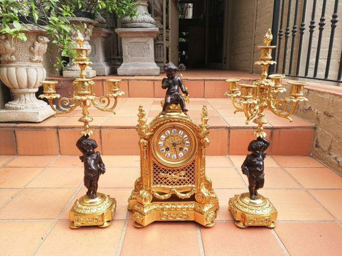 A Late 19th Century Gilt-Metal And Bronzed Clock Garniture Set With Candle Snuffer