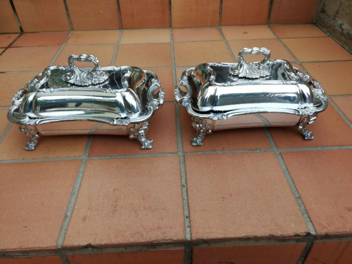 A pair of very large silver-plate entrée dishes standing on feet