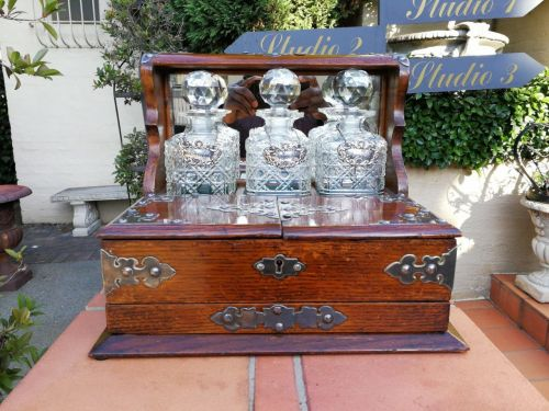 Oak and silver-plate tantalus with three decanters with three London silver wine labels